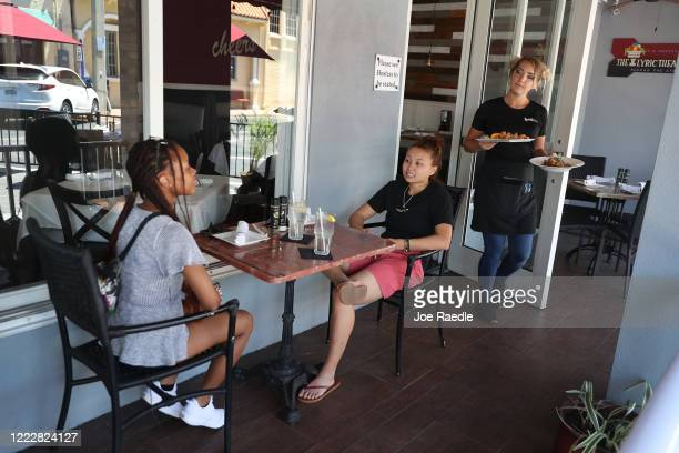 Brigitte Staples serves Crescent Wigfall and Lily Garrecht as they sit at the Spritz City Bistro, as the state of Florida enters phase one of the...