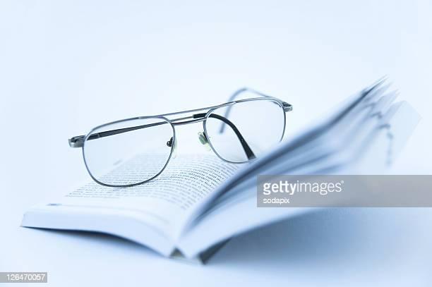 brille liegt auf einem buch - brille stock pictures, royalty-free photos & images