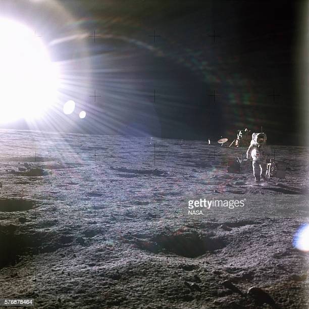 A brilliant sun shines above the Apollo 12 base on the Moon's surface One of the astronauts walks away from the lunar module Intrepid | Location near...