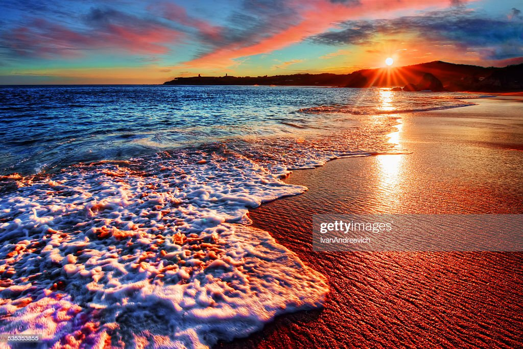 Brilliant vacation beach sunrise with colorful sand and distant cliffs : Stock Photo