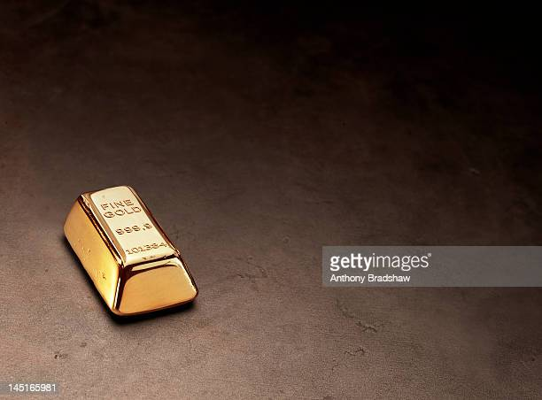 Brilliantly shiny gold ingot on dark background