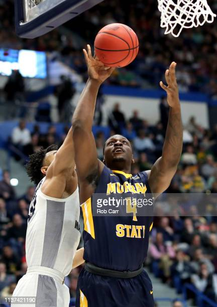 Brion Sanchious of the Murray State Racers looks for the basket against Theo John of the Marquette Golden Eagles during their first round game of the...
