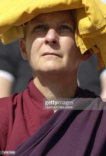 An Australian Buddhist nun shields her eyes from the sun with her robe as she listens to Tibet's spiritual leader the Dalai Lama speak at Australia...