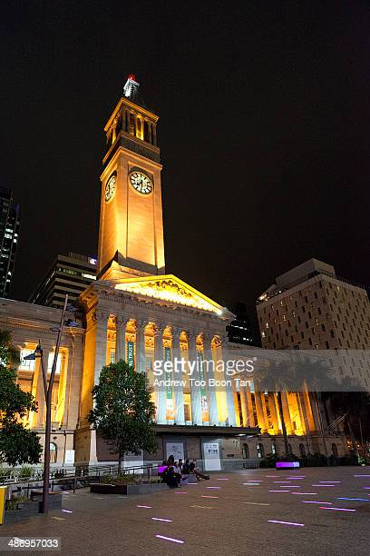 Brisbane City Hall with clock tower at night Short strips of decorative lights in the foreground