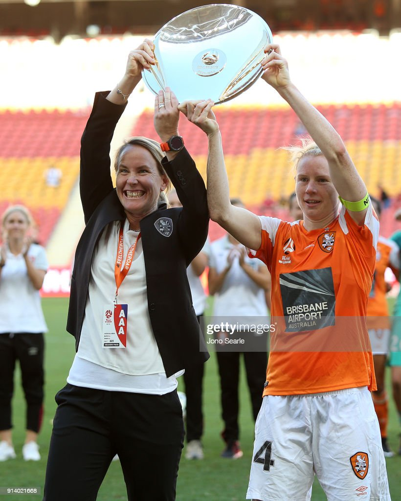 Brisbane coach Melissa Andreatta and captain Clare Polkinghorne celebrate with the premiership trophy after the win during the round 14 W-League match between the Brisbane Roar and Canberra United at Suncorp Stadium on February 4, 2018 in Brisbane, Australia.