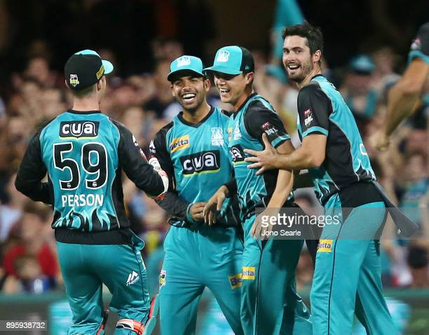 Brisbane player Mitch Swepson celebrates with team mates Shadab Khan and Ben Cutting after taking a catch during the Big Bash League match between...