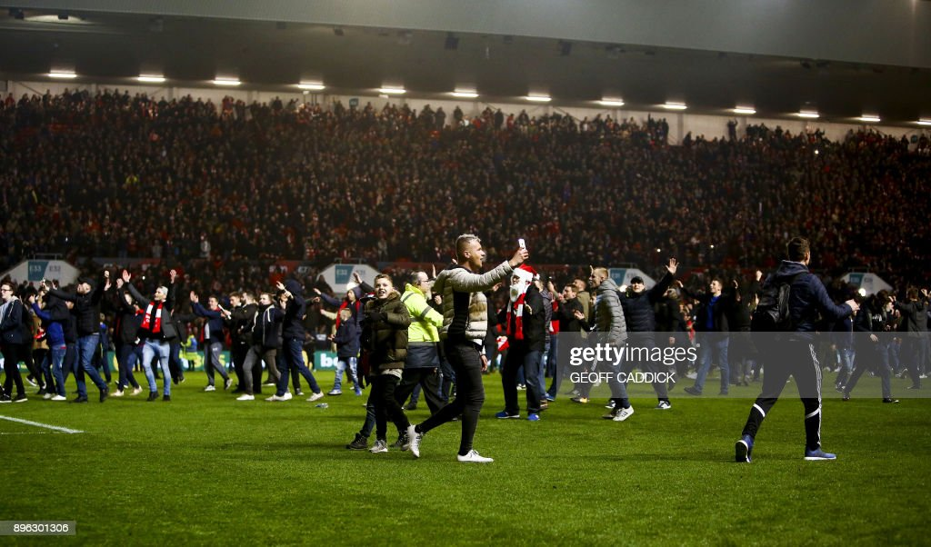 TOPSHOT - Bristol City fans celebrate their victory as they invade the pitch after the English League Cup quarter-final football match between Bristol City and Manchester United at Ashton Gate Stadium in Bristol, southwest England on December 20, 2017. / AFP PHOTO / Geoff CADDICK / RESTRICTED TO EDITORIAL USE. No use with unauthorized audio, video, data, fixture lists, club/league logos or 'live' services. Online in-match use limited to 75 images, no video emulation. No use in betting, games or single club/league/player publications. /