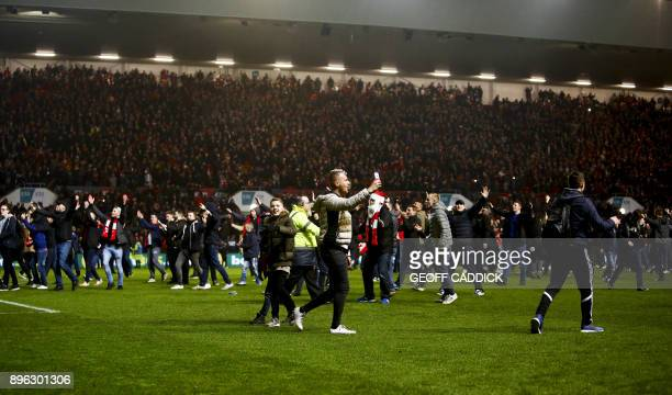 TOPSHOT Bristol City fans celebrate their victory as they invade the pitch after the English League Cup quarterfinal football match between Bristol...