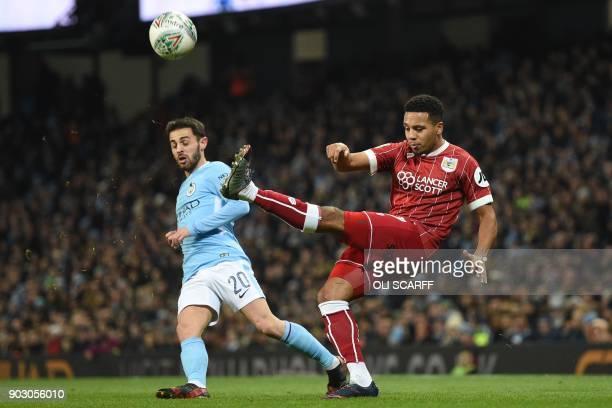 Bristol City's English midfielder Korey Smith clears the ball under pressure from Manchester City's Portuguese midfielder Bernardo Silva during the...