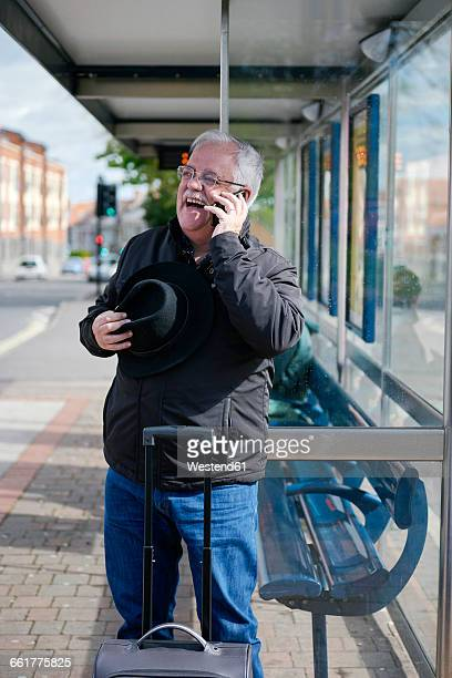 UK, Bristol, portrait of laughing senior man telephoning with smartphone while waiting at bus stop