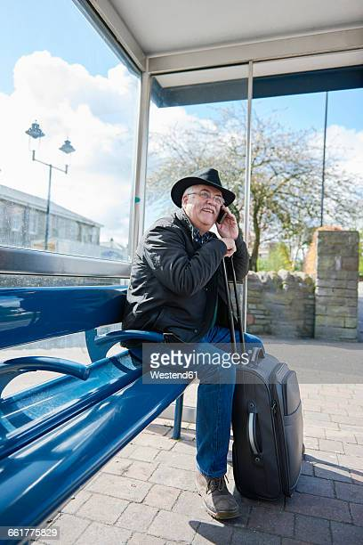 UK, Bristol, portrait of smiling senior man telephoning with smartphone while waiting at bus stop
