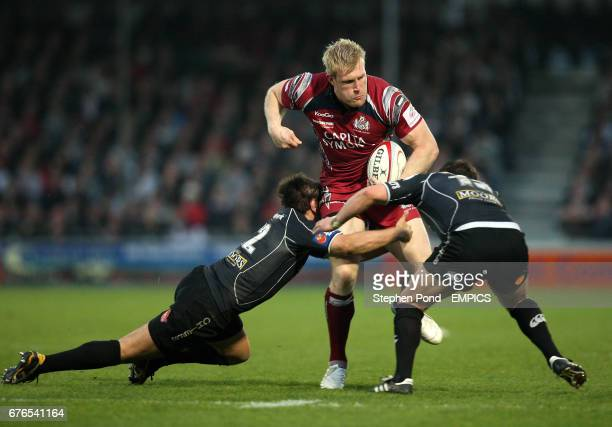 Bristol Rugby's Lee Robinson is tackled by Exeter Chiefs' Nic Sestaret and Matt Jess