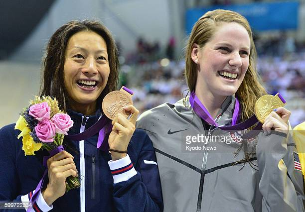 LONDON Britain Aya Terakawa of Japan holds up her bronze medal with gold medalist Missy Franklin of the United States during the award ceremony for...