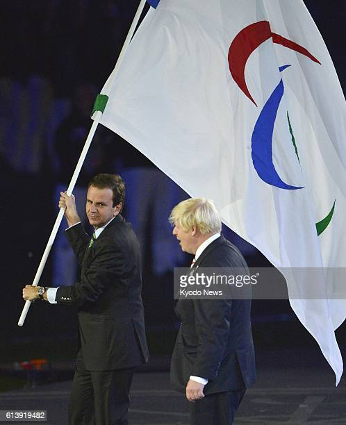LONDON Britain Eduardo Paes the mayor of Rio de Janeiro host city of the 2016 Olympic and Paralympic Games carries the Paralympic Flag which was...