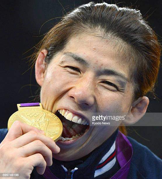 Britain - Japan's Saori Yoshida bites the gold medal she won in the women's wrestling 55-kilogram class at the 2012 London Olympics, at the ExCeL...