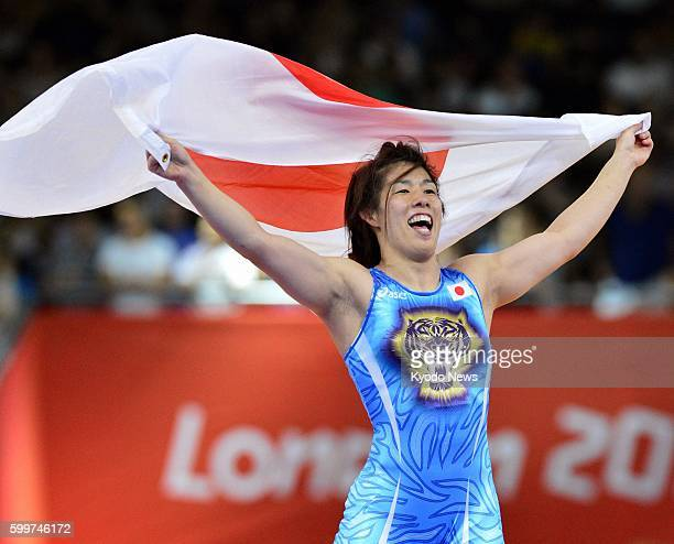 Britain - Japan's Saori Yoshida celebrates with the Japanese national flag after winning the gold medal in the women's wrestling 55-kilogram class at...