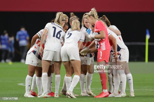 Britain players gather in a huddle before the start of the Tokyo 2020 Olympic Games women's group E first round football match between Japan and...