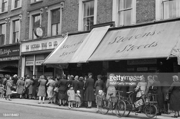 Rationing And Food Shortages In Wartime London England UK Women and children queue past several shops to buy goods from 'Patsy' the greengrocer on a...