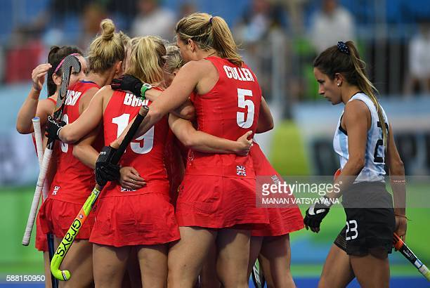TOPSHOT Britain team members celebrate a goal as Argentina's Maria Campoy walks past during the women's field hockey Britain vs Argentina match of...