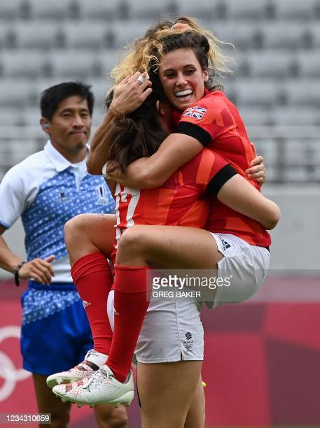 Britain's Abbie Brown congratulates teammate Lisa Thomson after she scored during the women's pool A rugby sevens match between Britain and Kenya...