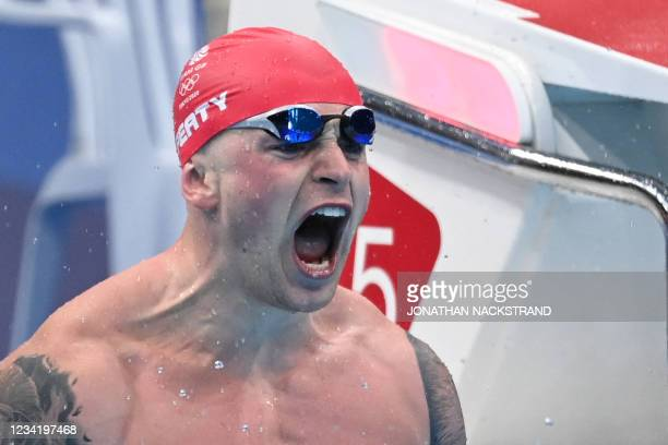 Britain's Adam Peaty celebrates winning to take gold in the final of the men's 100m breaststroke swimming event during the Tokyo 2020 Olympic Games...