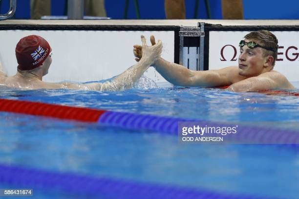 Britain's Adam Peaty celebrates with Britain's Ross Murdoch after breaking the world record in the Men's 100m Breaststroke heat during the swimming...