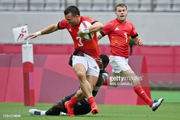 Britain's Alex Davis is tackled by Fiji's Jerry Tuwai in the men's pool B rugby sevens match between Fiji and Britain during the Tokyo 2020 Olympic...