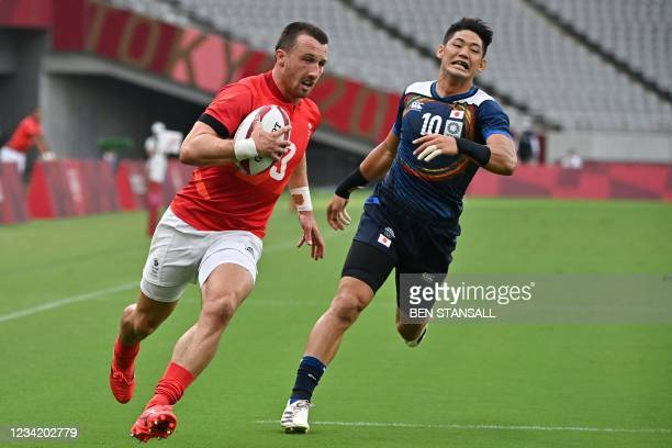 Britain's Alex Davis runs past Japan's Yoshikazu Fujita to score a try in the men's pool B rugby sevens match between Britain and Japan during the...