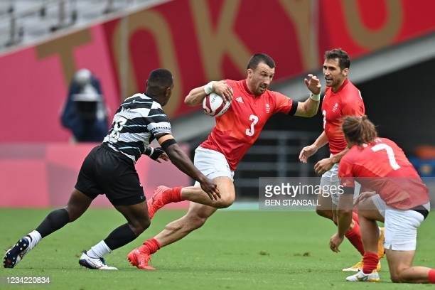 Britain's Alex Davis tries to break through Fiji's defence in the men's pool B rugby sevens match between Fiji and Britain during the Tokyo 2020...