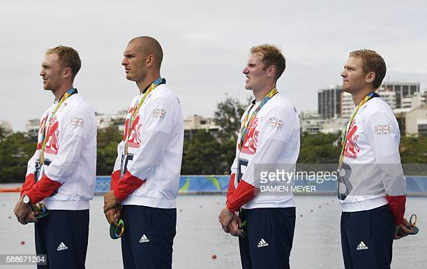Britain's Alex Gregory Britain's Constantine Louloudis Britain's George Nash and Britain's Mohamed Sbihi listen to the national anthem on the podium...