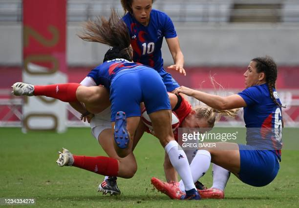 Britain's Alex Matthews is tackled by France's Coralie Bertrand and Fanny Horta during the women's rugby sevens semi-final match between France and...