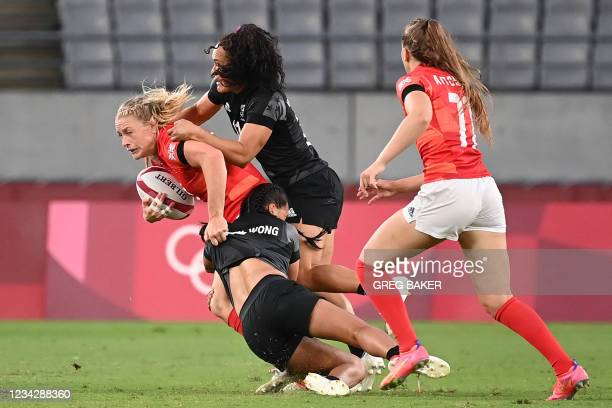 Britain's Alex Matthews is tackled by New Zealand's Tyla Nathan-Wong and Potia Woodman during the women's pool A rugby sevens match between the...