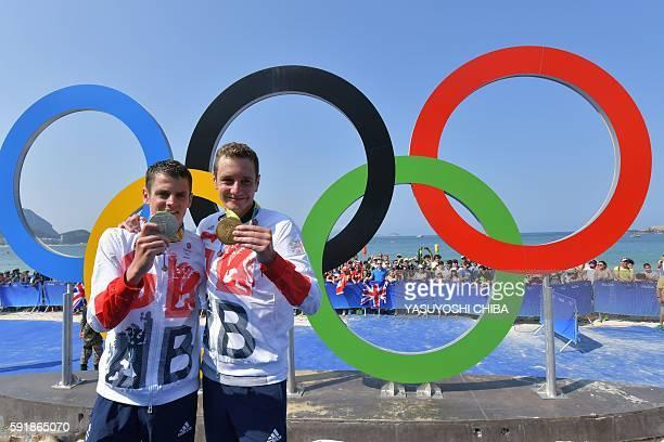 البريطاني أليستير براونلي والبريطاني جوناثان براونلي يقفان بميداليتيهما بجوار الحلقات الأولمبية بعد الترياتلون الرجال في فورت ...
