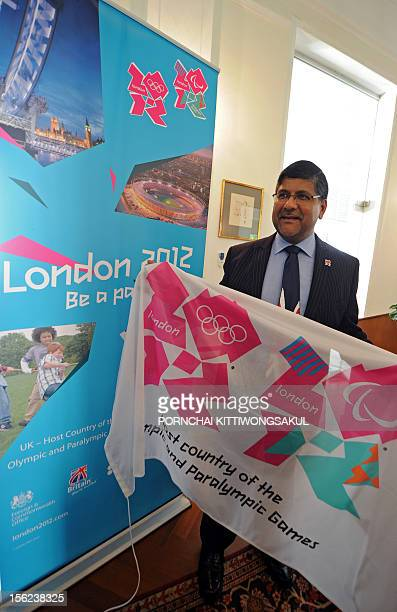 Britain's ambassador to Thailand Asif Ahmad holds a campaign flag for the London 2012 Olympic Games to mark 99 days to go before the start of the...