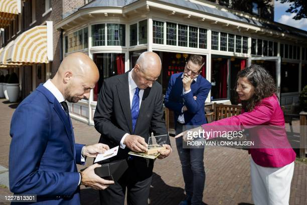 Britain's Ambassador to The Netherlands' Peter Wilson and Canada's Ambassador to The Netherlands' Lisa Helfand receive the first copy of the mint set...