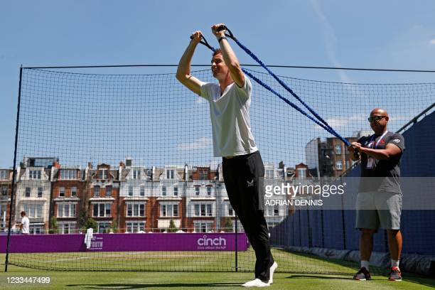 Britain's Andy Murray does stretching exercises as he practices ahead of his first round match against France's Benoit Paire during the ATP...