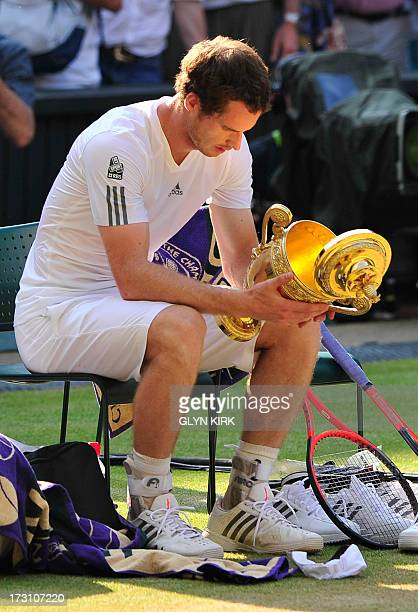 Britain's Andy Murray looks at the winner's trophy as the lid falls off during the presentation after beating Serbia's Novak Djokovic in the men's...