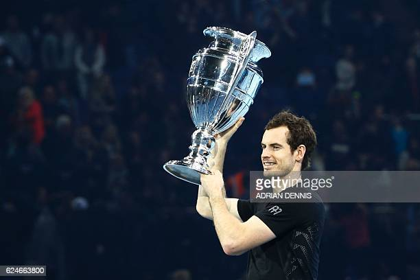 Britain's Andy Murray poses holding the ATP World Number One trophy after winning the men's singles final against Serbia's Novak Djokovic on the...