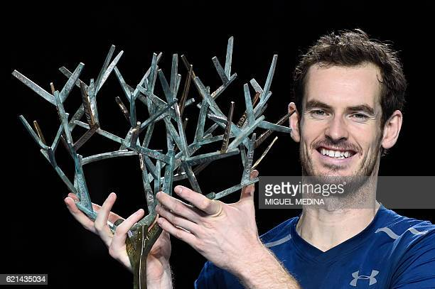 Britain's Andy Murray poses with his trophy on the podium after winning the final tennis match against USA's John Isner at the ATP World Tour Masters...