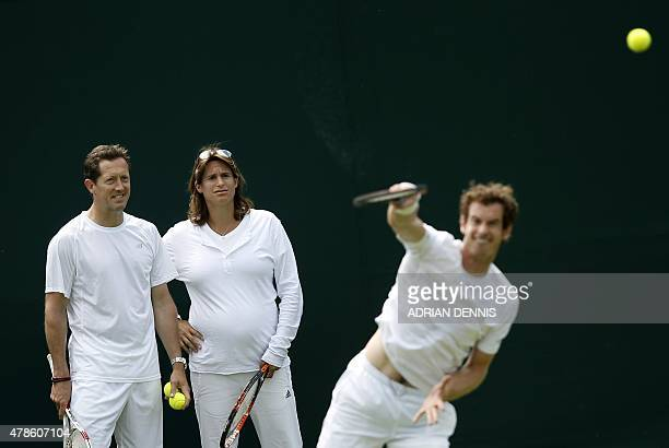 Britain's Andy Murray practices serving by Swedish Coach Jonas Bjorkman and French Coach Amélie Mauresmo during a practice session ahead of the...