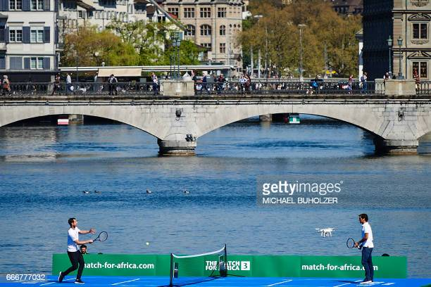 Britain's Andy Murray returns a ball to Switzerland's Roger Federer during a promotion on a raft on the river Limmat before a charity tennis match on...