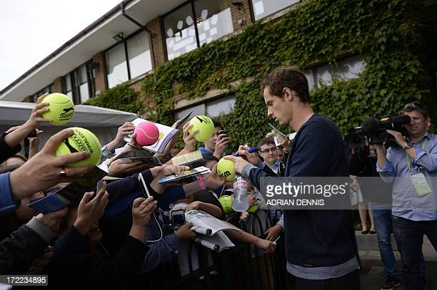 Britain's Andy Murray signs autographs for fans after a training session at the practice courts on day eight of the 2013 Wimbledon Championships...