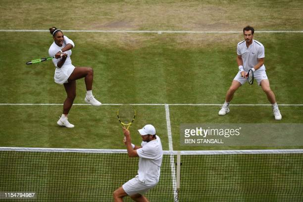 TOPSHOT Britain's Andy Murray stands by as US player Serena Williams returns against France's Fabrice Martin and US player Raquel Atawo unseen during...