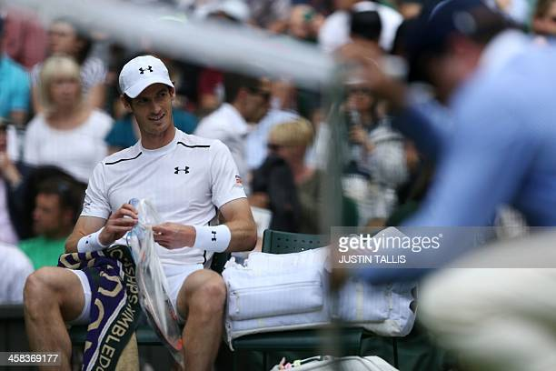 Britain's Andy Murray unwraps a fresh racquet in the break between games against Australia's John Millman during their men's singles third round...