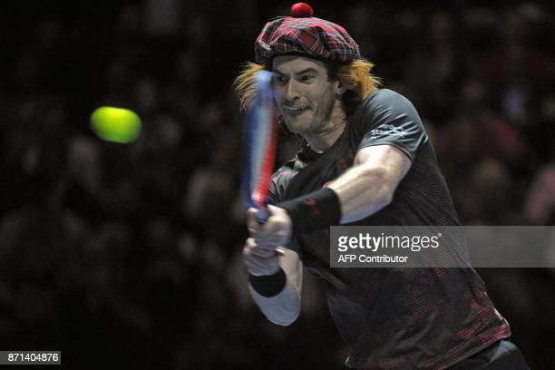 TOPSHOT Britain's Andy Murray wears a tartan hat as he returns to Switzerland's Roger Federer in their exhibition tennis singles match during 'Andy...