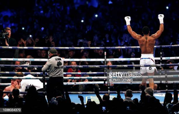 TOPSHOT Britain's Anthony Joshua celebrates as the referee tends to Russia's Alexander Povetkin after he was knocked out during their boxing world...