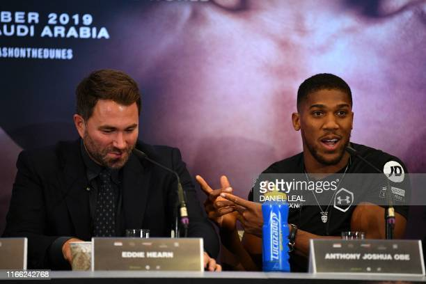 Britain's Anthony Joshua gestures to promoter Eddie Hearn at promotional press conference for the Clash on the Dunes fight against MexicanUS WBA IBF...