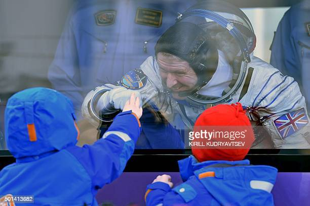 Britain's astronaut Tim Peake gestures to his children from a bus after his space suit was tested at the Russianleased Baikonur cosmodrome prior to...