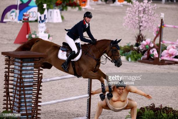 Britain's Ben Maher riding Explosion W jumps past a small sumo statue in the equestrian's jumping individual finals during the Tokyo 2020 Olympic...