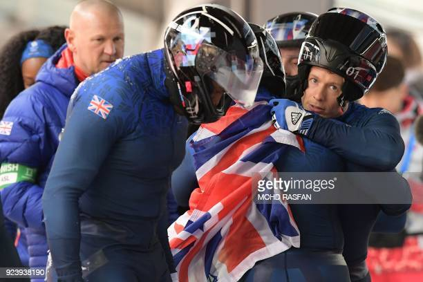 Britain's Ben Simons hugs his crew while holding a Union Jack flag after the 4man bobsleigh heat 4 final run during the Pyeongchang 2018 Winter...
